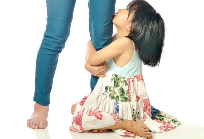 clingy child embracing mother's leg