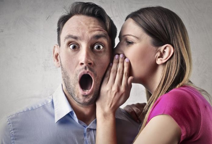 woman whispering something to a shocked man
