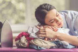 woman sleeping on top of pile of clothes after ironing