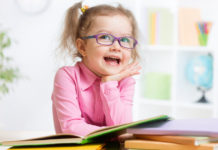little girl wearing eyeglasses smiling with her bunch of books