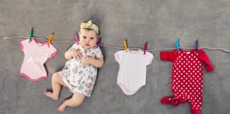 baby girl in white flowery dress and head scarf hanging with the laundry of onesie