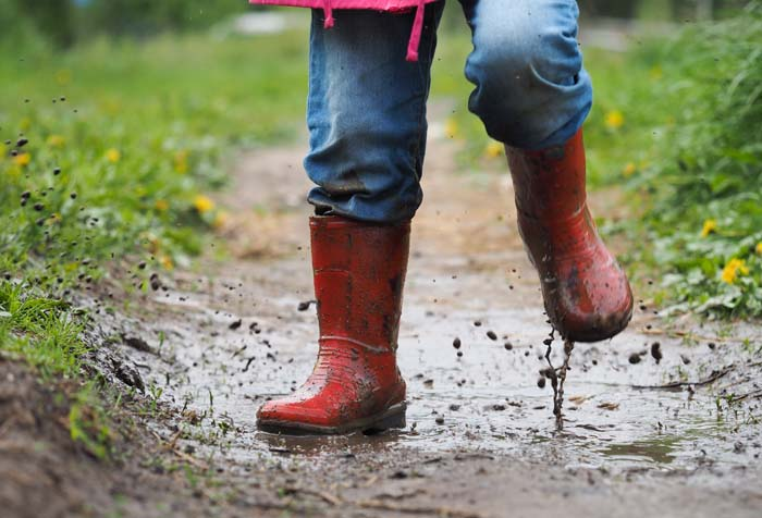 child in blue jeans wearing red muddy boots in the puddle