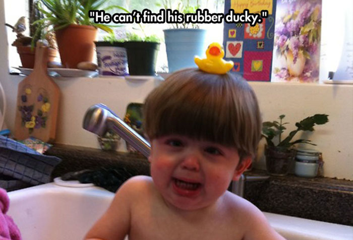 BCrying baby in wash tub with rubber ducky on his head