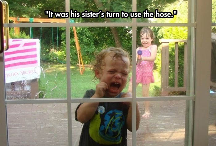 Crying child at the door while sister hoses him with water