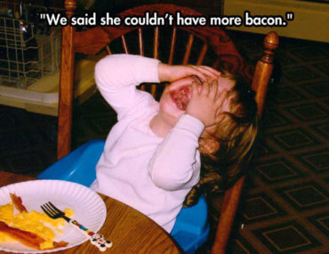 Crying child at the table with her bacon and eggs meal