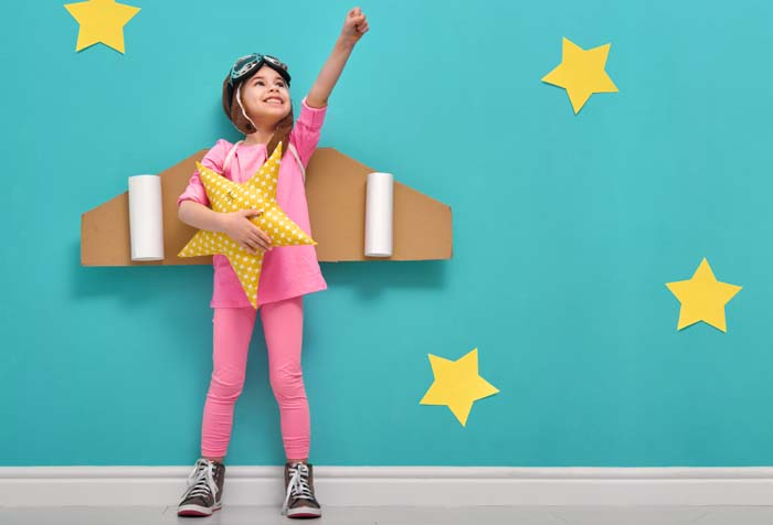 Little girl in an astronaut costume dreaming of becoming a spaceman on a background of bright blue wall with yellow stars