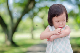 little girl in outdoors surrounded and biten by mosquitoes