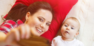 mother and child in bed with red pillow taking selfie