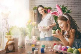 mother and daughter wearing bunny ears painting easter eggs