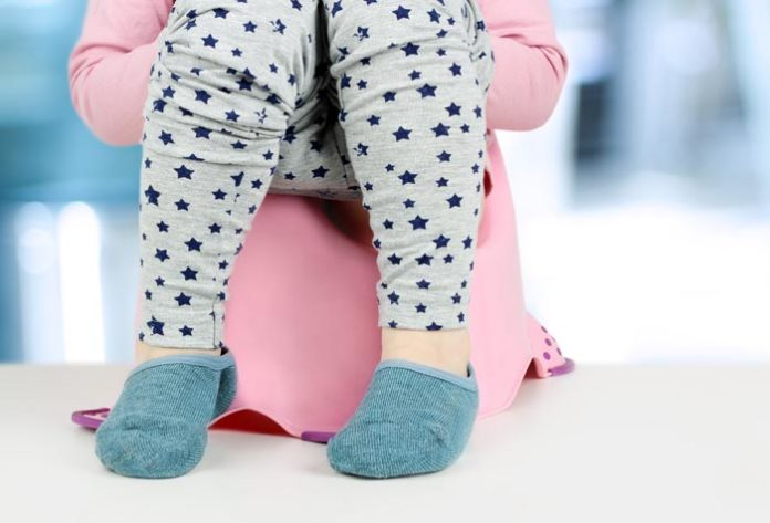 child wearing navy socks, stary grey pajama and pink sweater sitting in pink potty