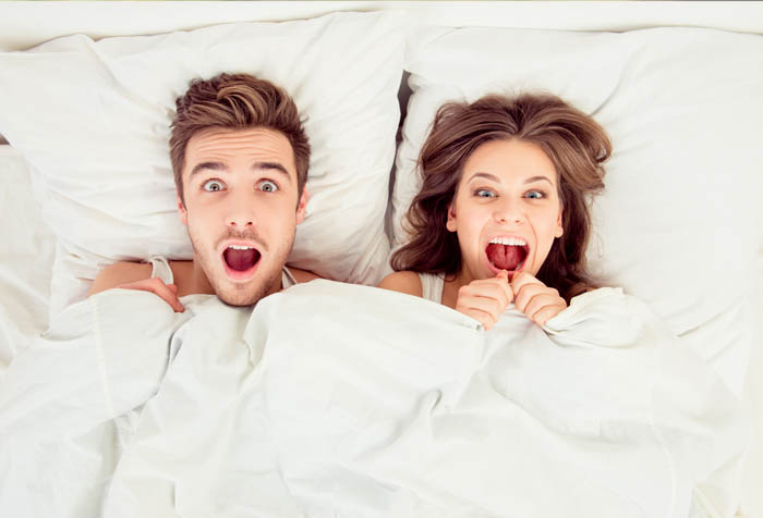 Mum and Dad shocked and excited in bed under all white beddings