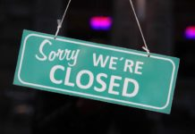 green and white sorry we're closed sign in black bokeh background