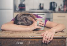 woman sleeping in a wooden table while holding her cup of drink