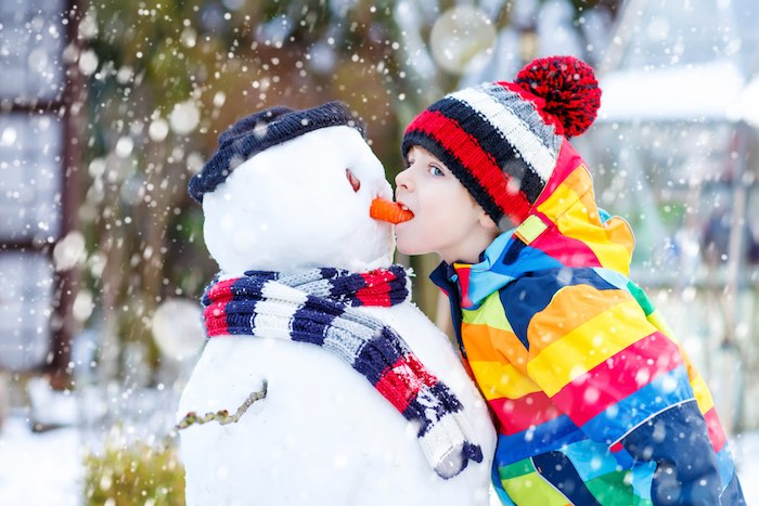 Funny kid boy in colorful clothes making a snowman, outdoors