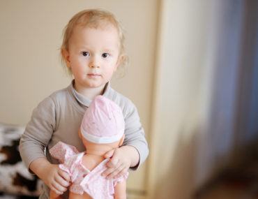 Boy hugging a baby doll in pink dress and a bonnet
