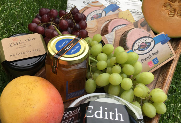 Cheeseboard ingredients on a tray with jams, melon, grapes and pates