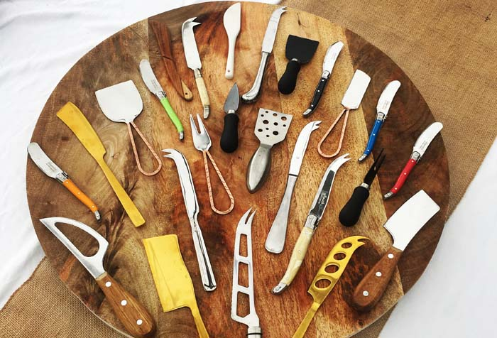 Cheeseboard knives and slicing utensils are spread out on a round wooden cheeseboard