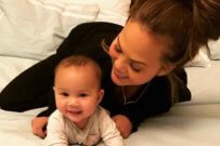 Chrissy Teigen taking care of her baby in white bed