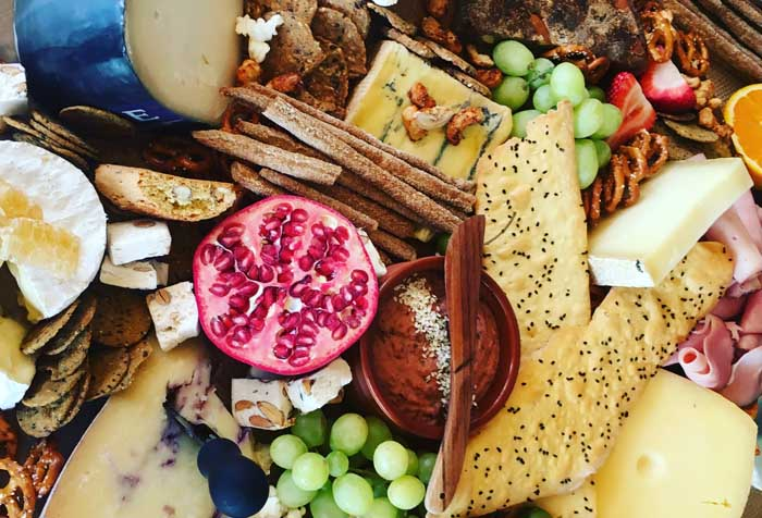 Many cheeseboard ingredients spread out showing cheese, fruits and pastries