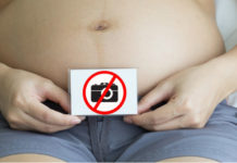 Pregnant woman showing tummy holding a no photo symbol with two hands