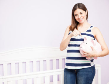 Pregnant Woman on striped shirt holding a piggy bank beside a white crib