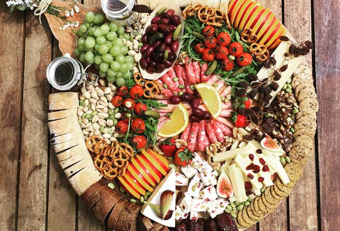 Round cheeseboard presentation with all the ingredients presented nicely on a wooden table with different kinds of cheese, fruits and pastries.