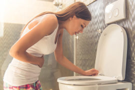Woman in white sleeveless shirt feeling sick and leaning on a toilet showing first signs of pregnancy