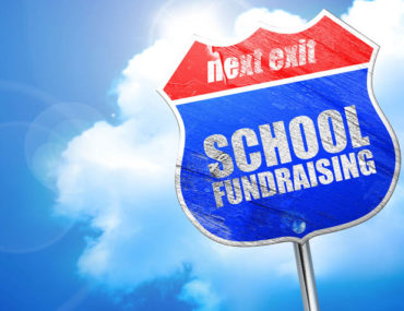 School fundraising sign printed on a traffic sign with the word next exit on a blue cloudy sky background