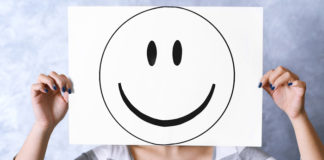 Woman holding a smiley face drawn on a white paper covering her face