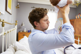 things new babies do, dad holding baby with smelly nappy