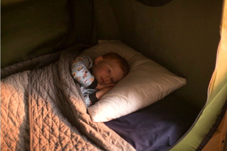 child asleep in pop-up bed tent