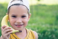 child talking on banana phone to illustrate mobile phone plans for kids