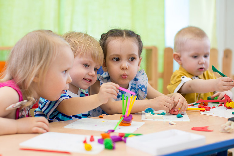 Toddlers at activity table at childcare