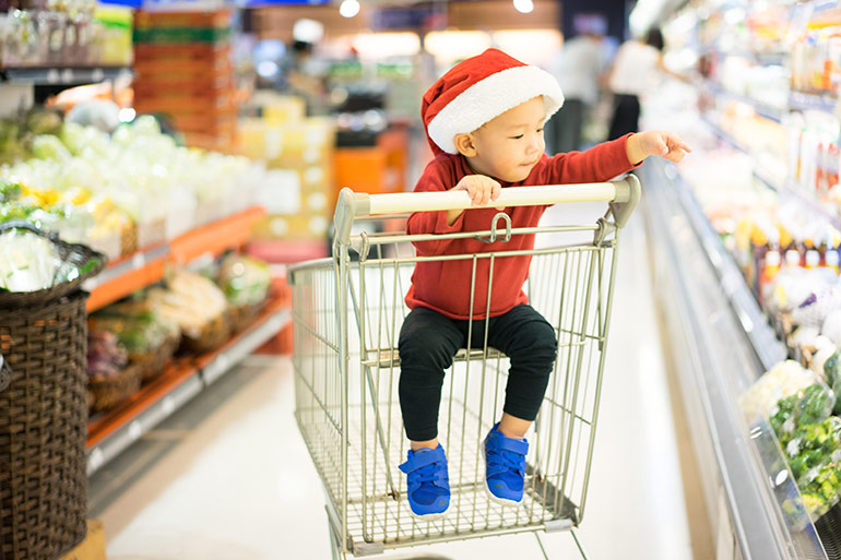 Child in shopping trolley, santa hat, supermarket