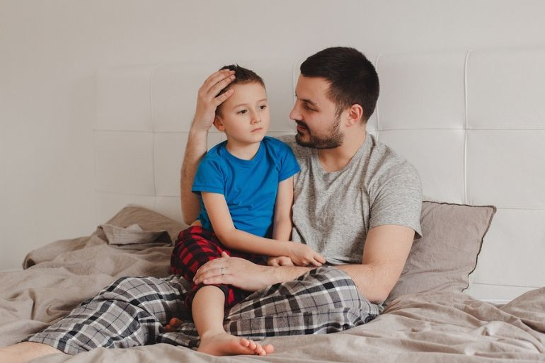 young boy and dad sat on bed talking