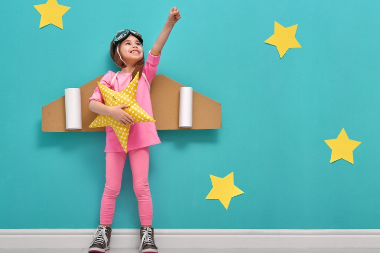 Child wearing cardboard aeroplane wings and reaching for the stars