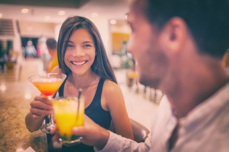 Couple drinking cocktail at bar, date night