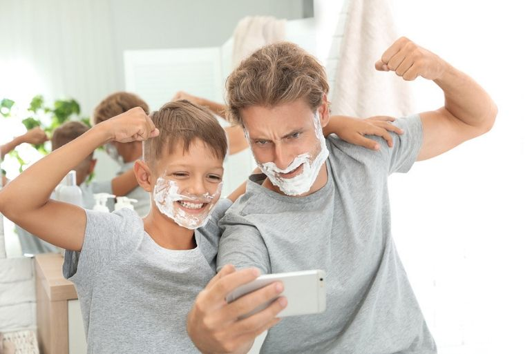 Dad and son taking selfie with shaving foam on their faces