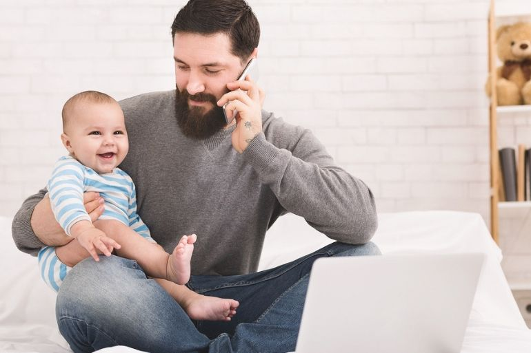 Dad at home holding baby and talking on phone \ parental leave