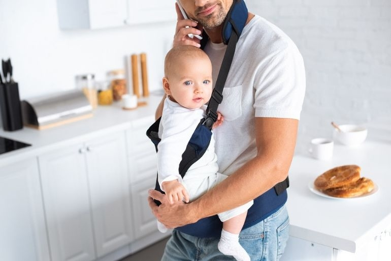 Dad with baby in carrier | parental leave