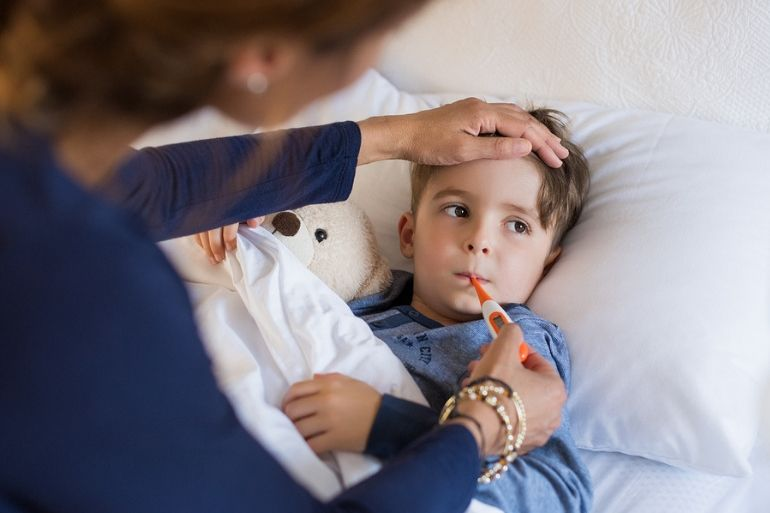 young boy in bed with mum taking his temperature   childrens cold and flu