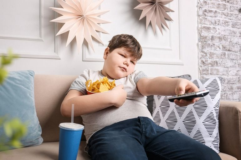 overweight boy on sofar with TV remote and chips | childhood obesity