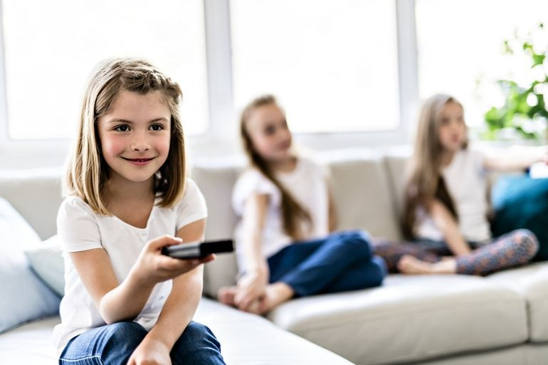 young girls sitting on sofa with TV remote