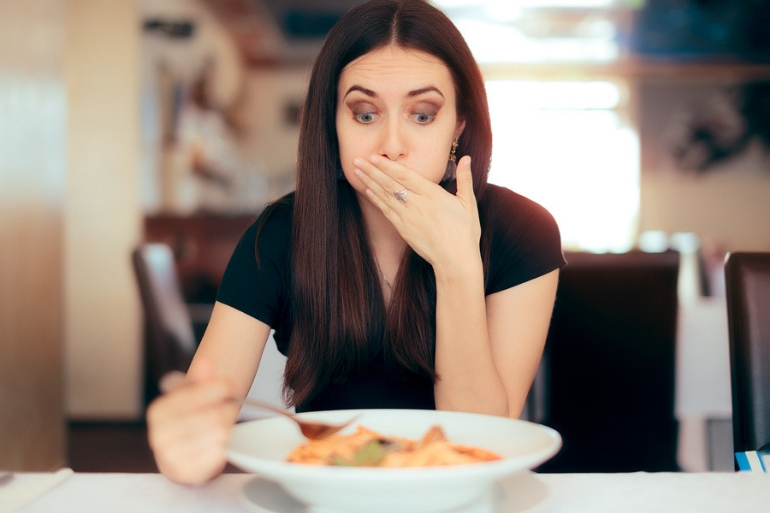 woman eating and feeling sick with hand over her mouth