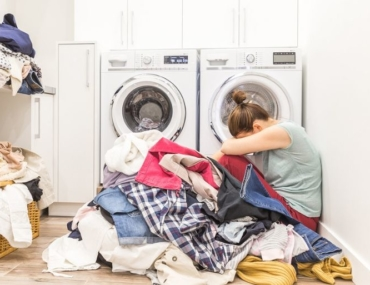 woman sitting on laundry floor with piles of clothes