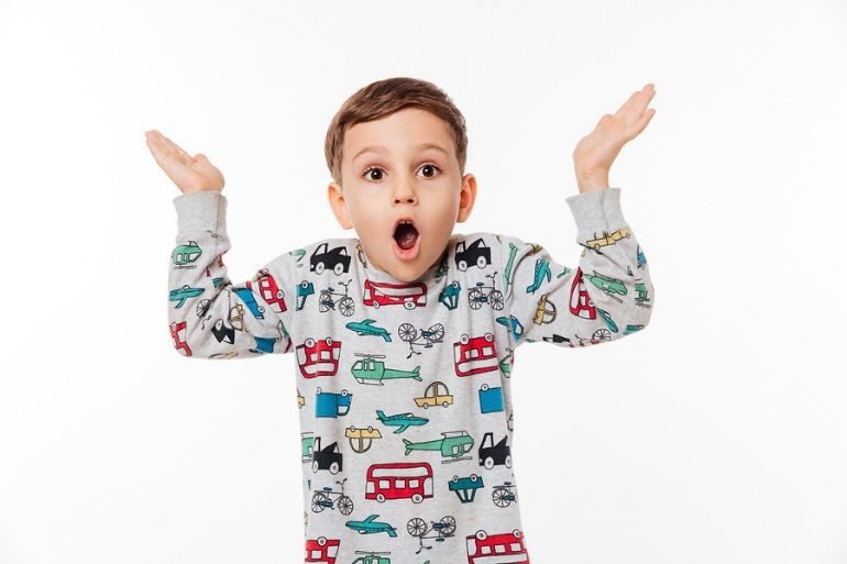 young boy in pyjamas hands in air looks surprised