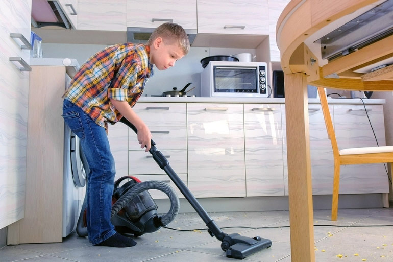 teen boy vacuuming kitchen floor
