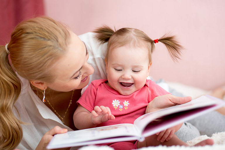 woman reading a book to toddler