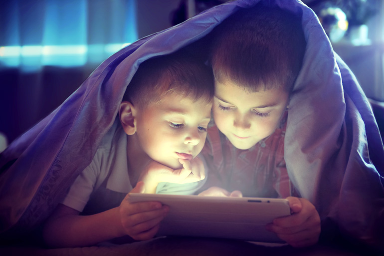 two young boys playing games on tablet under a doona