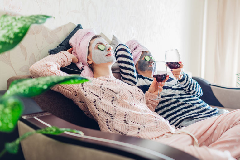 two women on sofa wearing face masks with wine in their hand | mum's night off